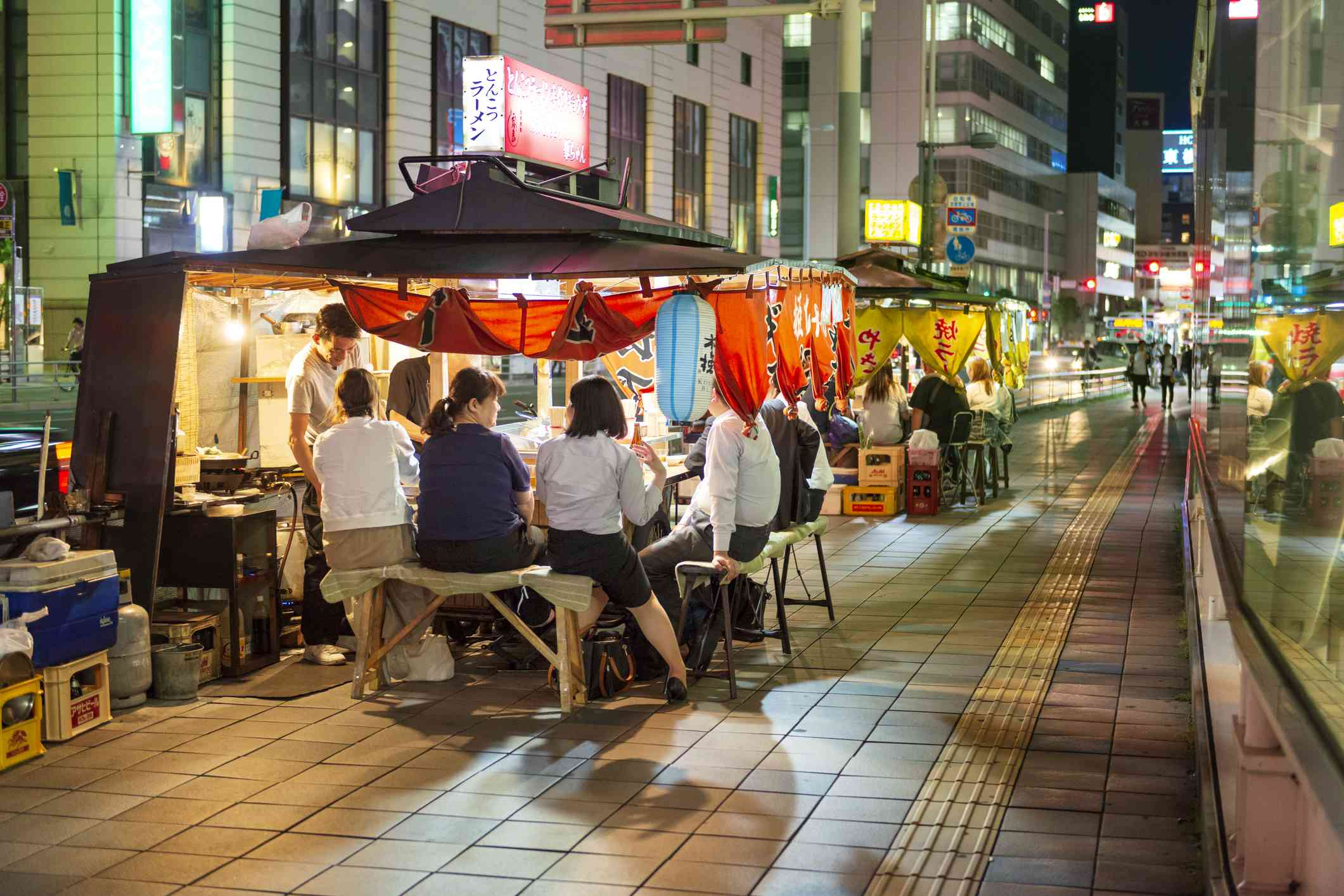 people sitting at various food stalls in fukuoka