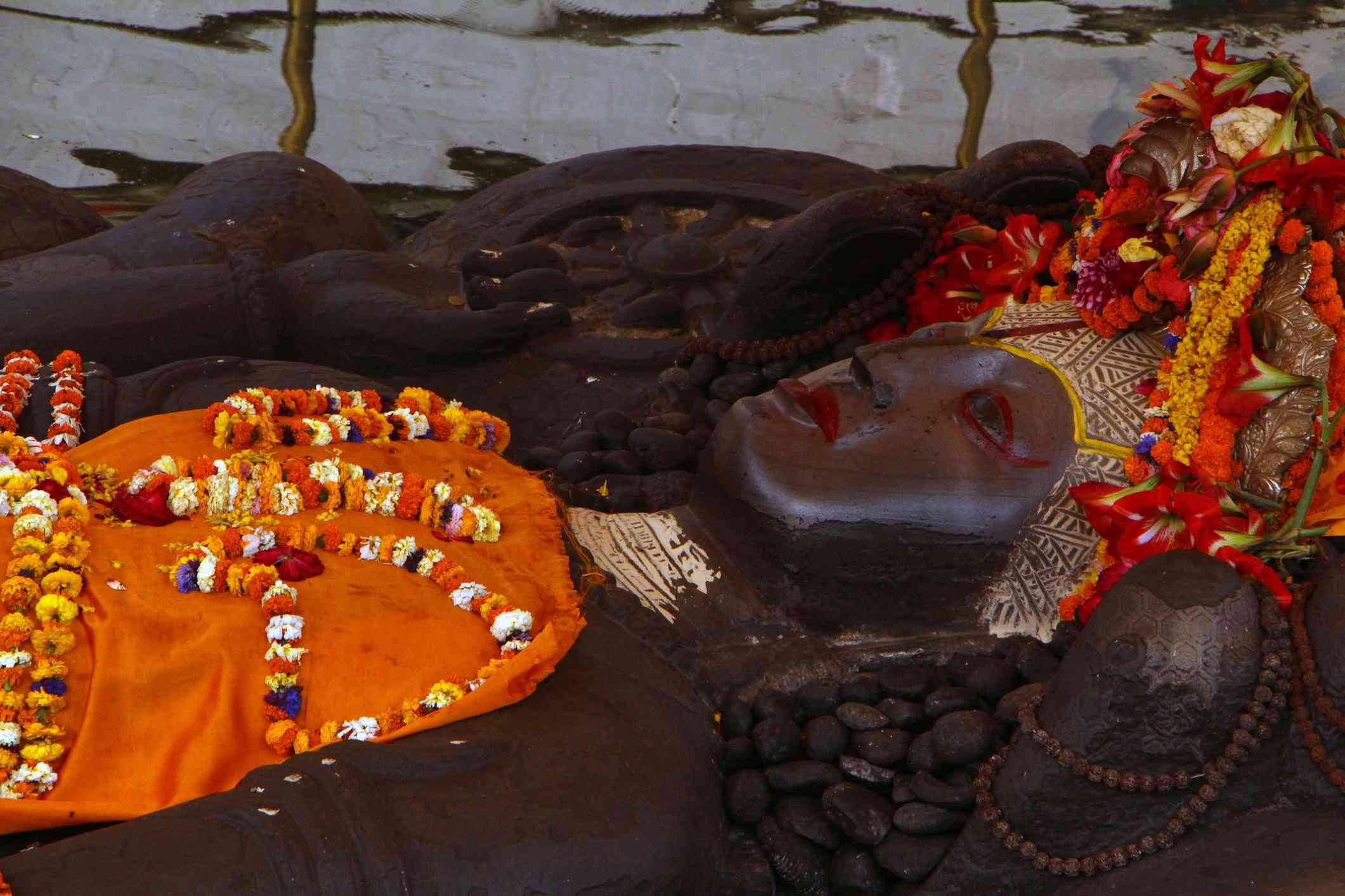 reclining statue of Hindu Lord Vishnu with orange marigold garlands