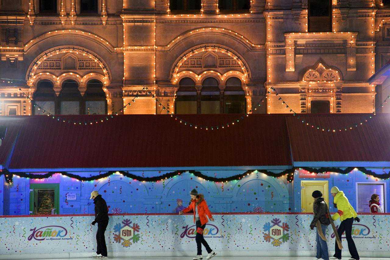 Russland, Moskau;  Jugendliche Schlittschuhlaufen vor dem riesigen Einkaufszentrum, das Gum, auf dem Roten Platz im Winter