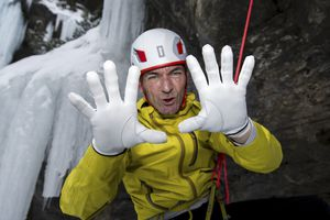 A climber showing his white gloves used for dry tooling climb.