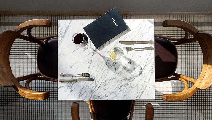 Overhead image of a marble table at Battuto with a menu, two sets of knives and forks and two glasses