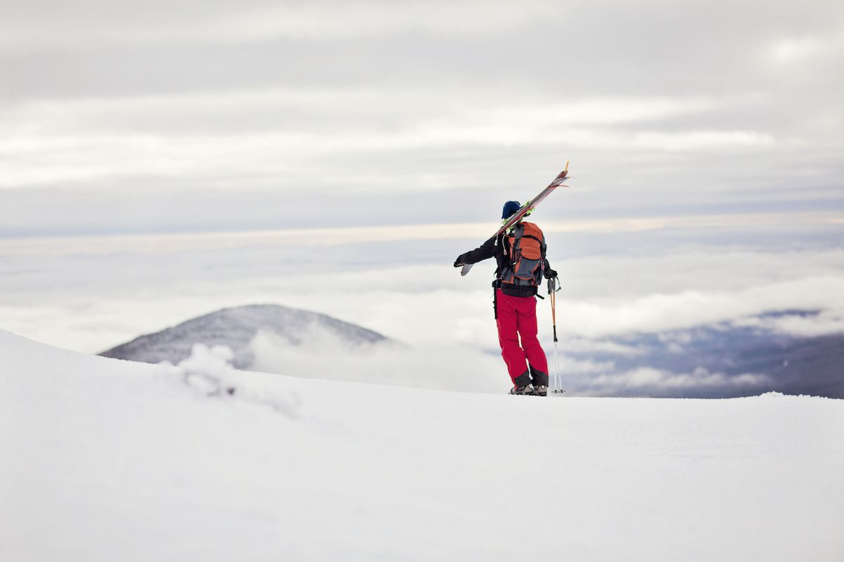 A skier carries his skis over his shoulder as he stands atop a mountain ridge.