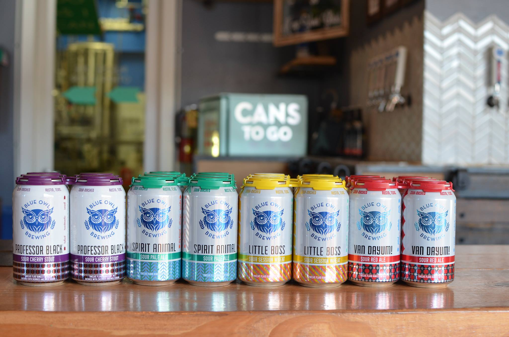colorful cans of beer at Blue Owl Brewing