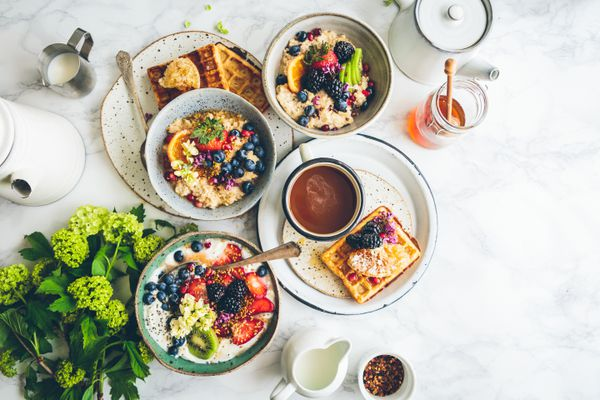 A picture looking down at a place setting for brunch, including a waffle, a yogurt parfait, some oatmeal, and tea