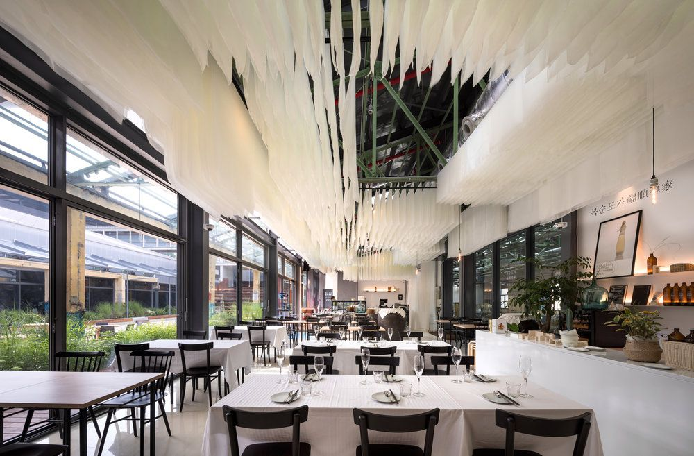 airy restaurant dining room with white cloths hanging from the ceiling
