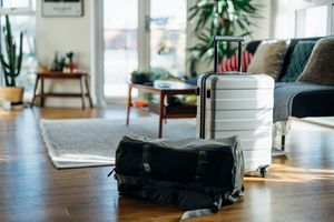 Still-life of suitcase and carry bag, on the floor of cool holiday apartment
