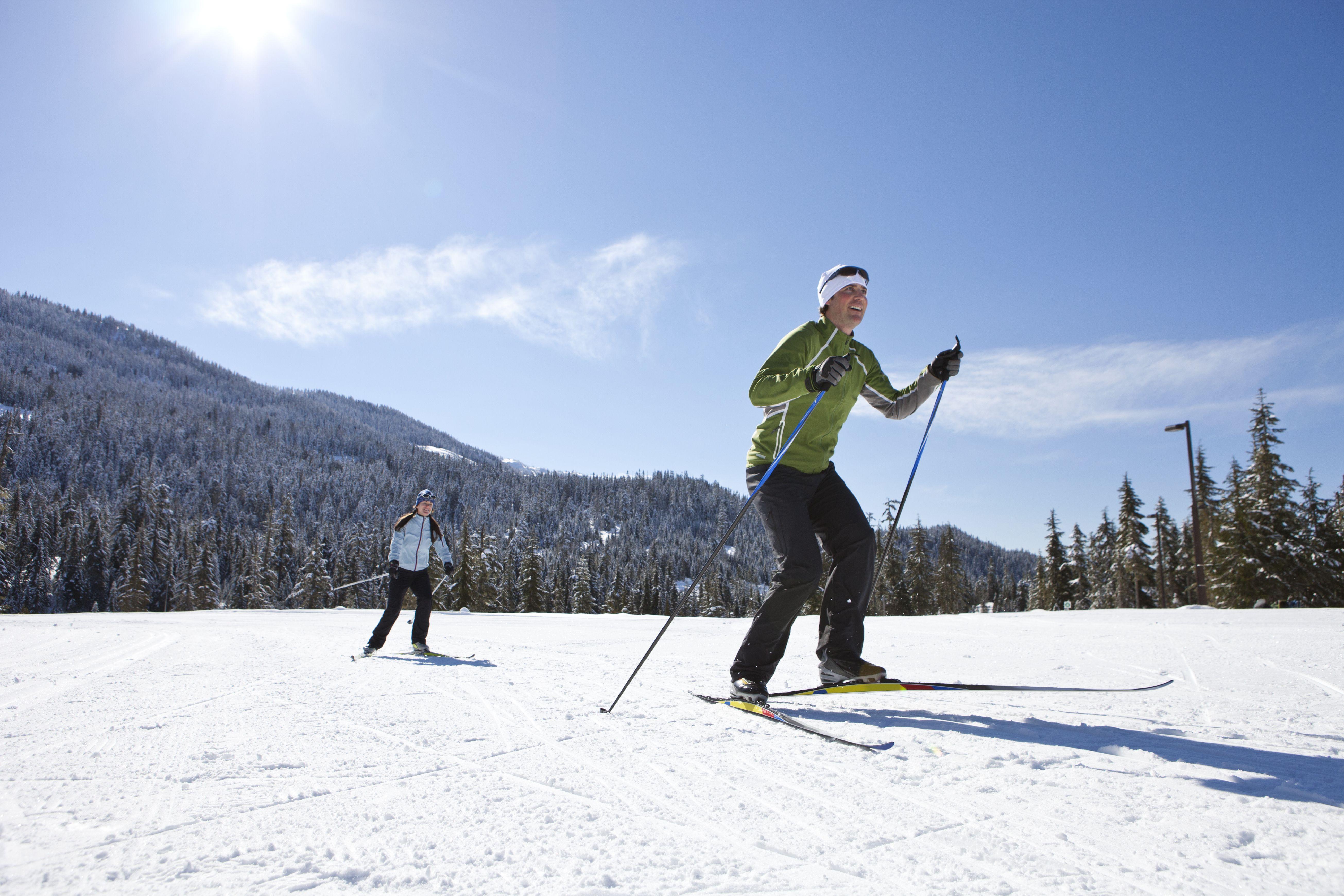 A young couple skis a Whistler run