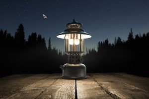 A vintage kerosene lantern shot at dusk on a picnic table in the darkened forest of the southern Sierra Nevada