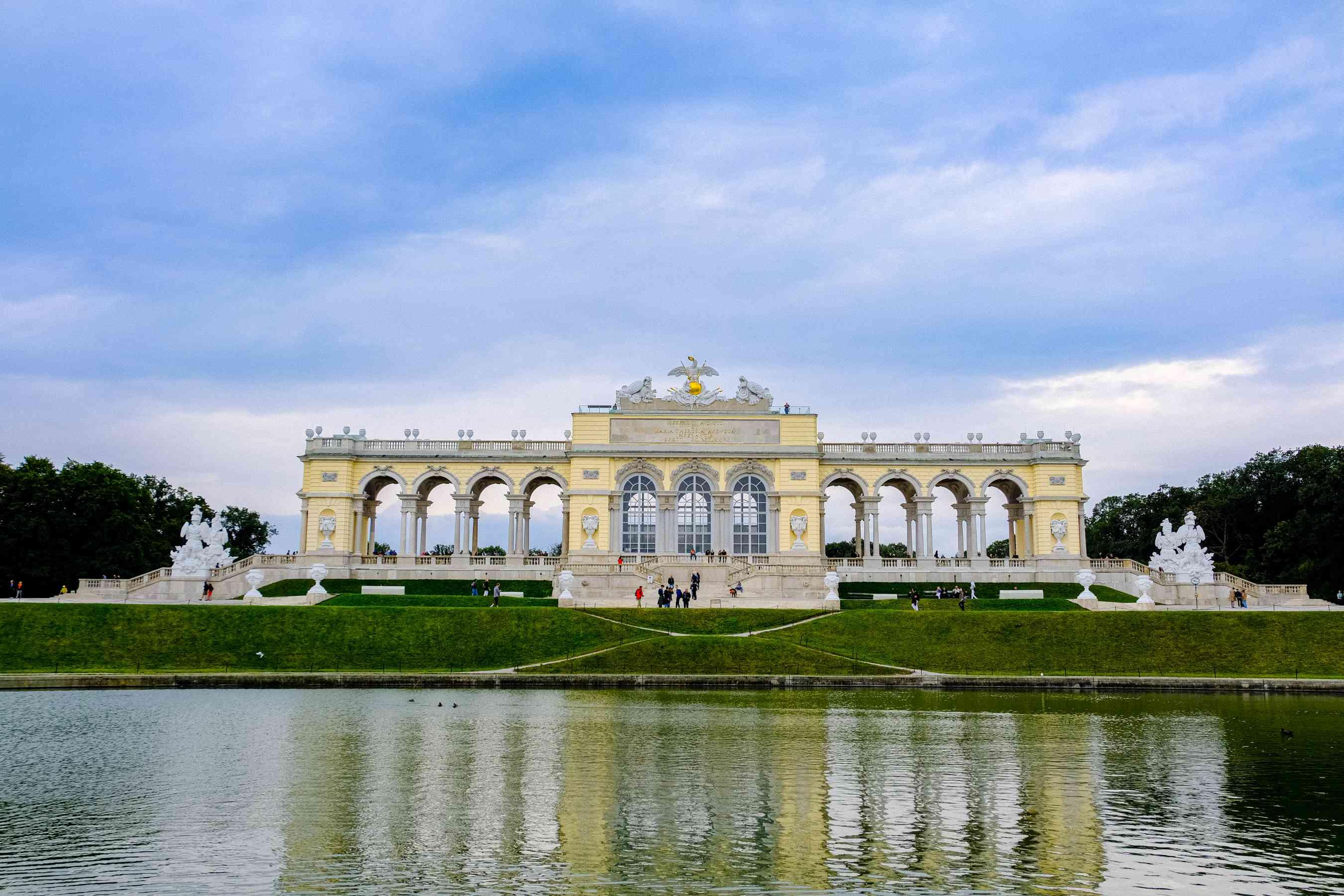 Personas de pie en una gran estructura exterior que forma parte del Palacio de Schonbrunn