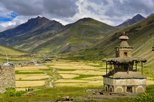 Buddhist stupa in foreground with wheat fields and mountains in background