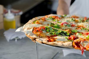 Close up of a pizza on a stand with fresh mozzarella, tomato sauce and basil on top