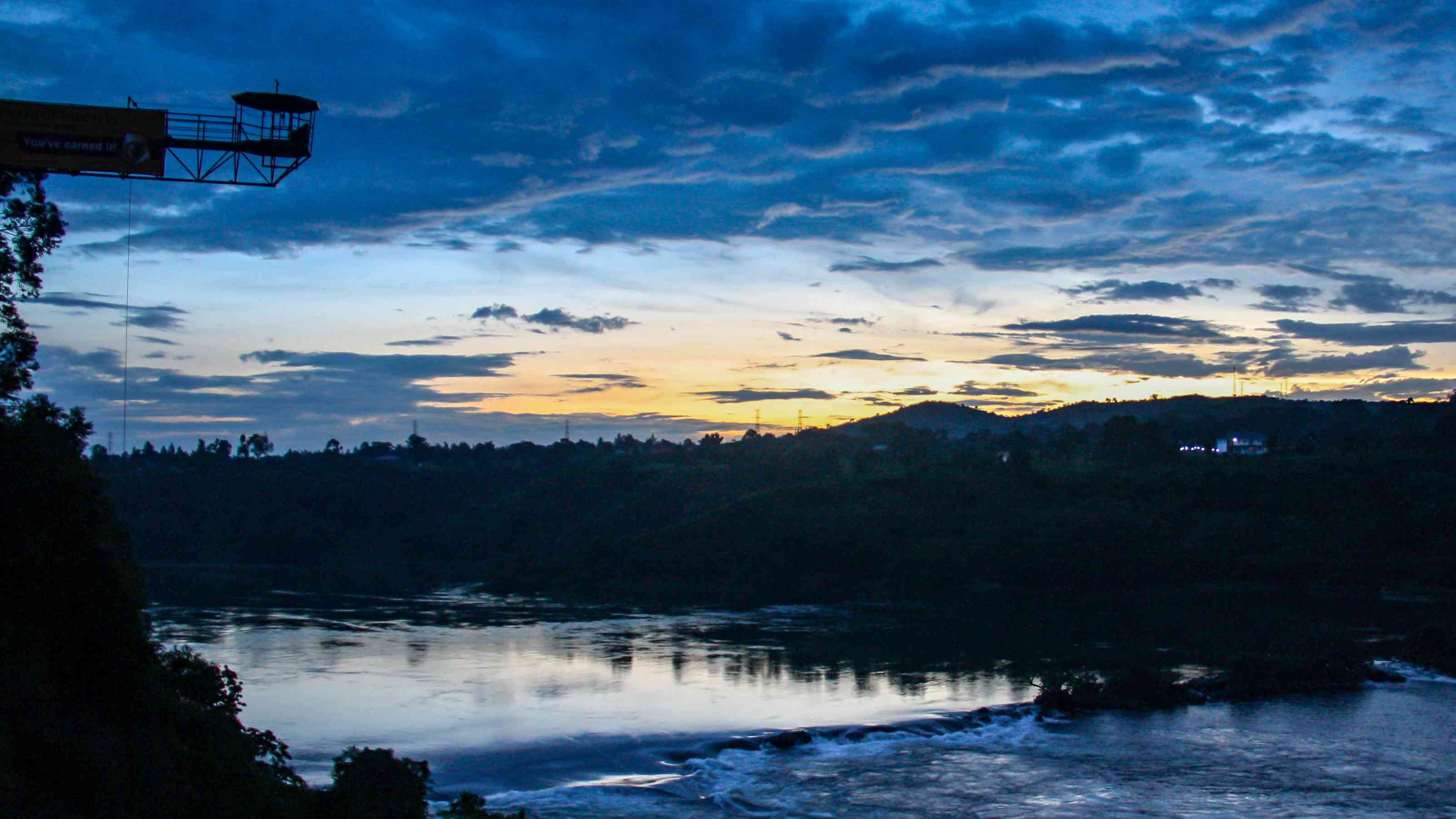 Sunset reflections over the Nile River and bungee jumping tower in Jinja, Uganda