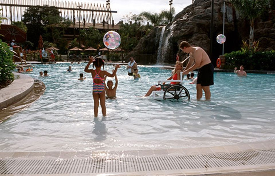 Lady in wheelchair enjoying a zero entry pool at Disney World.