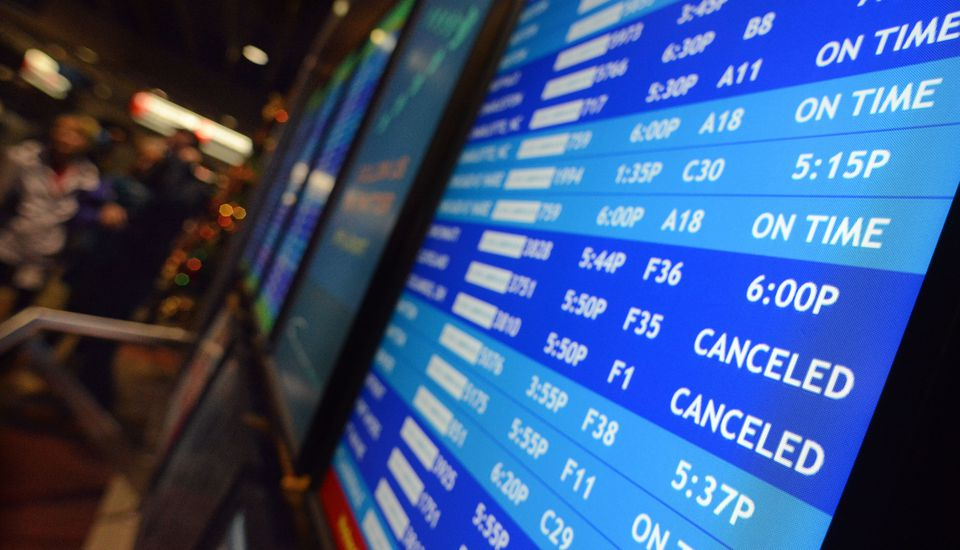 Flight departure displays indicate delayed or canceled fights