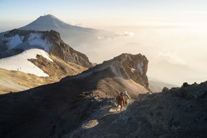 A couple running down from the summit of Iztaccihuatl volcano