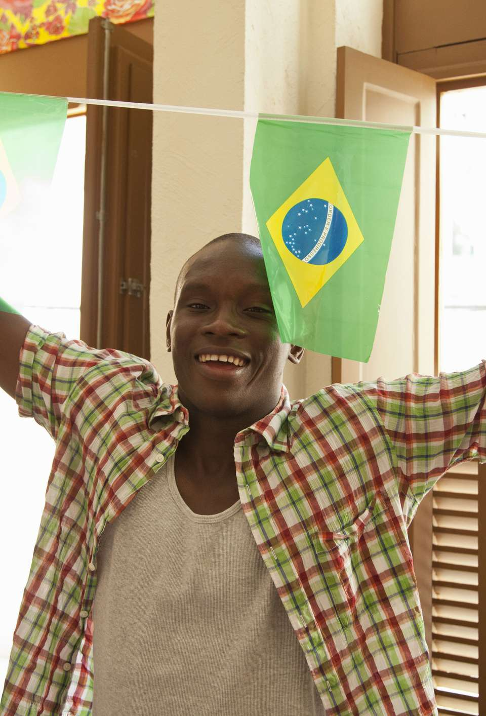 An exchange student poses with a string of Brazilian flags