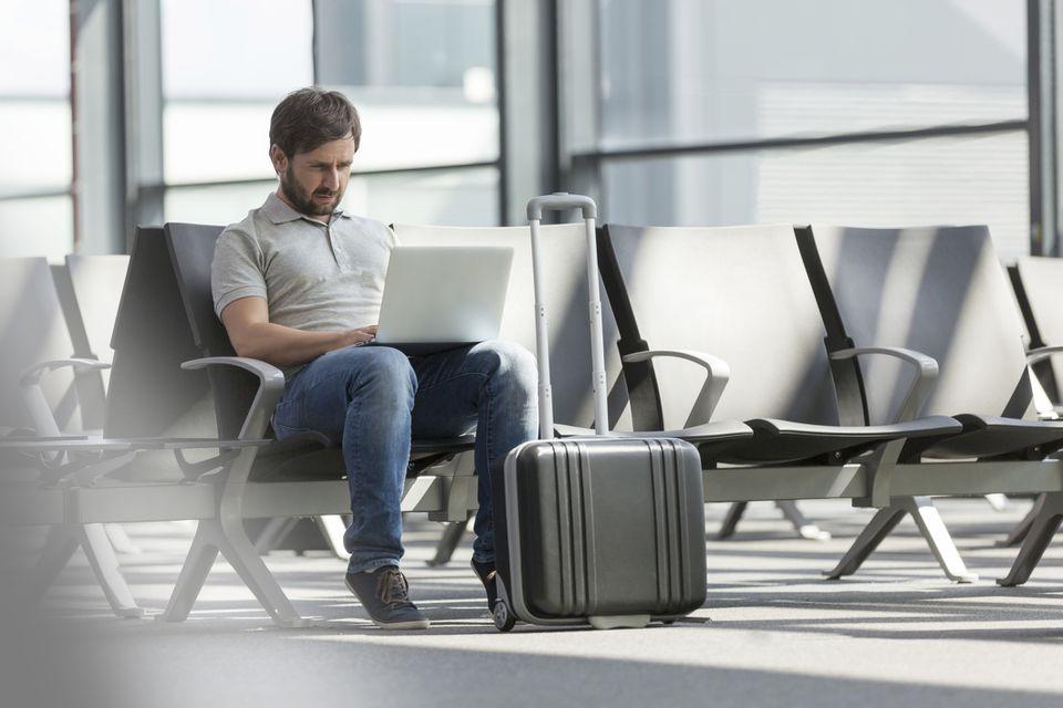 Hombre en la computadora portátil en el aeropuerto