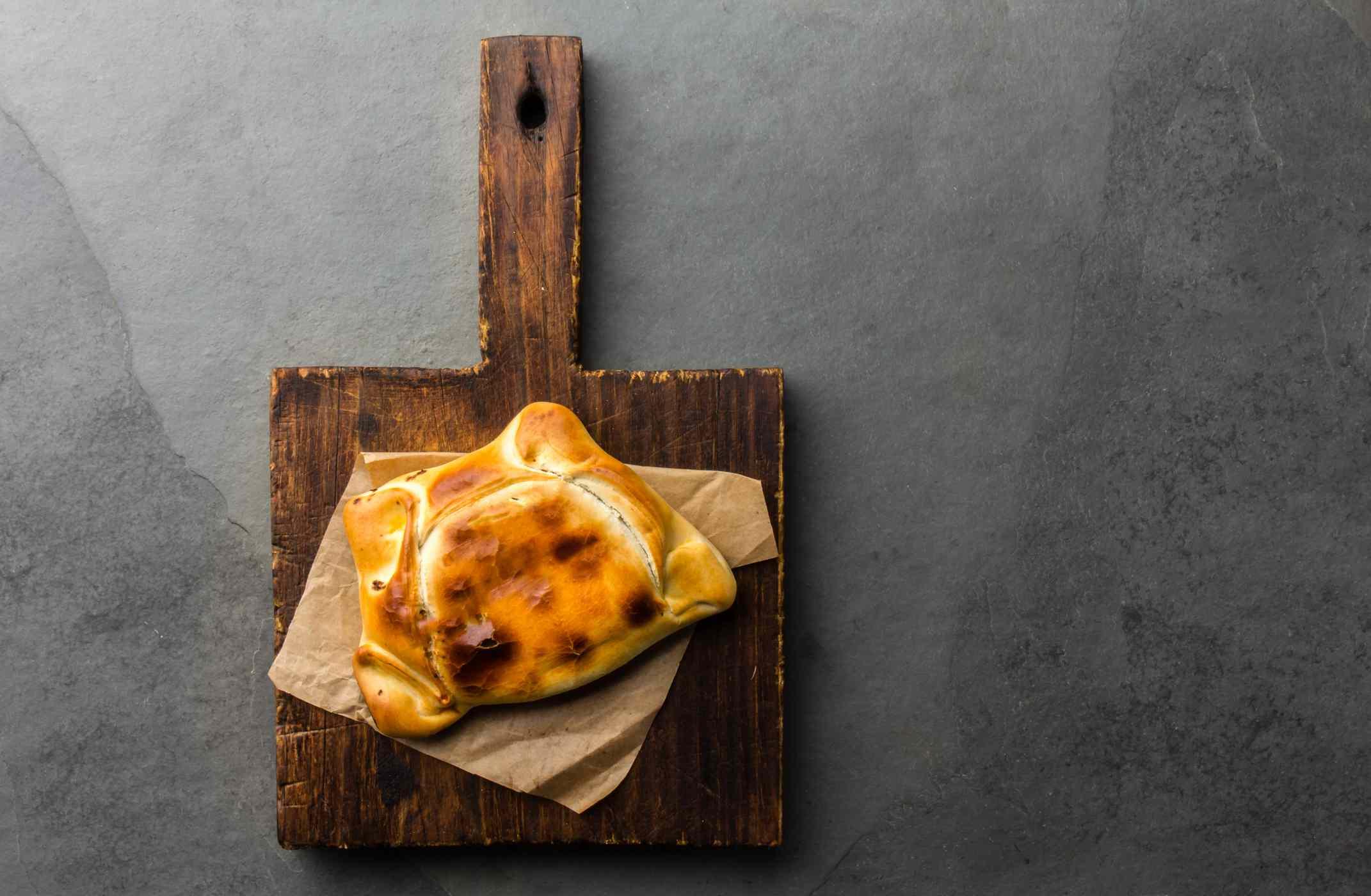 Chilean empanada on a wooden pizza board