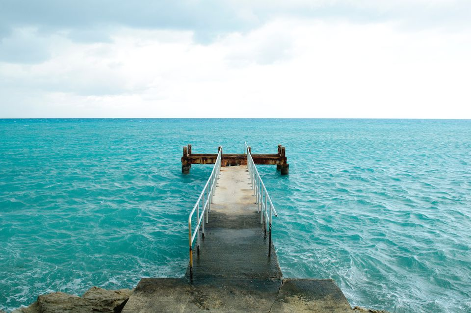 view of a stone pier going into blue waters
