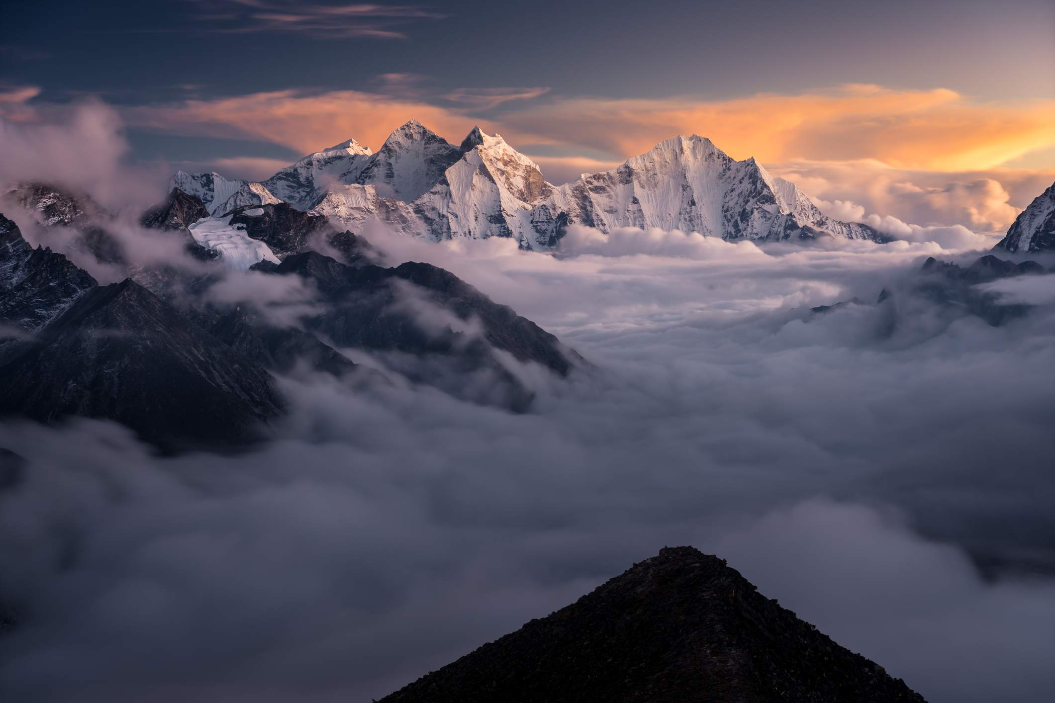 Peaks of the Himalayas above the clouds at sunset