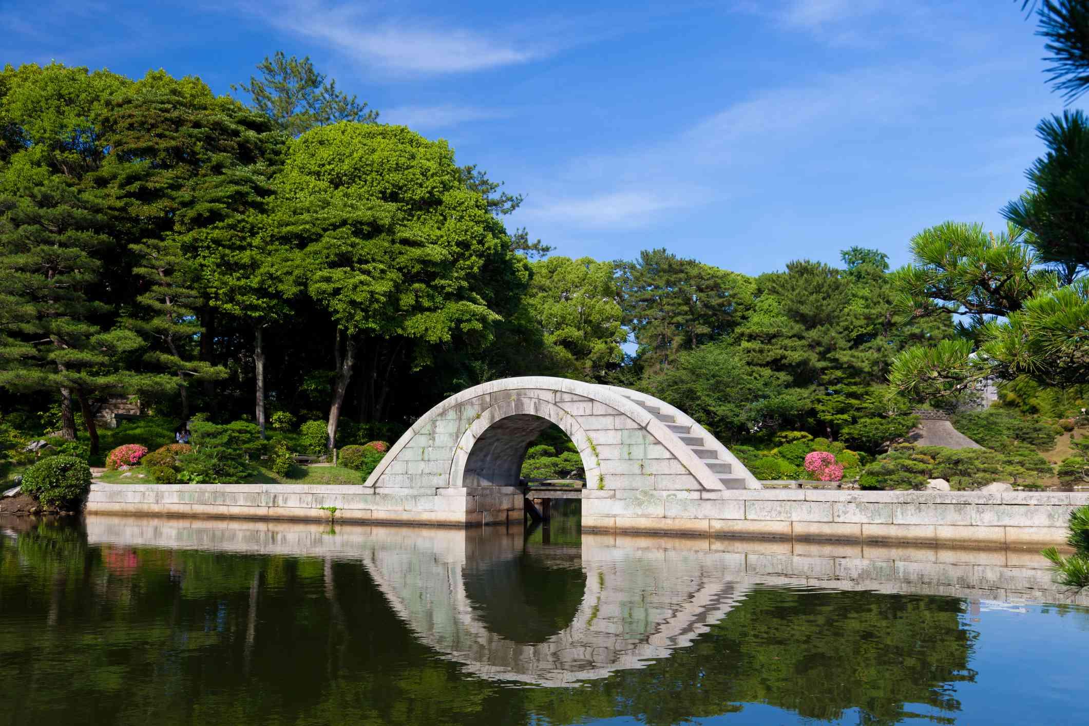 small stone bridge over a pond in a Garden in Hiroshima