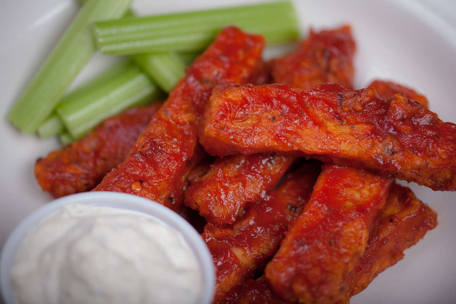 Vegan buffalo chicken with ranch dipping sauce and celery