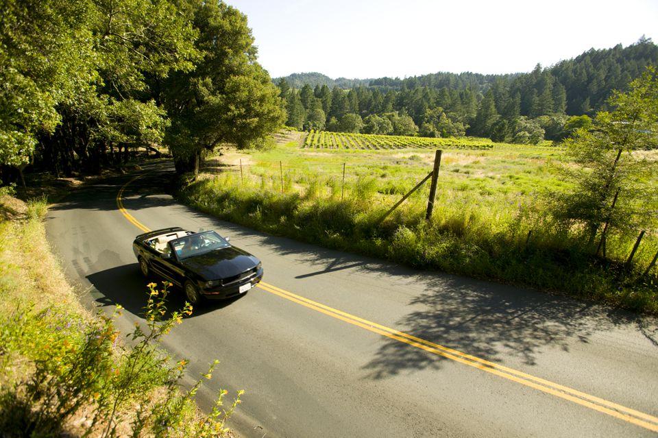 Pareja conduciendo descapotable, Napa Valley, California