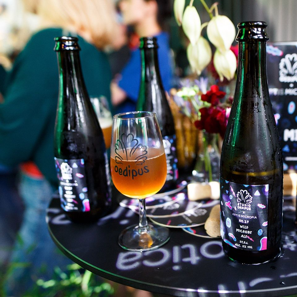 Three beer bottles and a glass of beer on a black table at an event