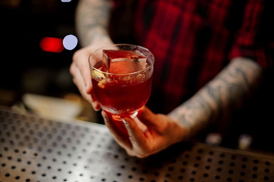 Bartender serving a glass of a Vieux Carre cocktail with big ice cube and orange zest