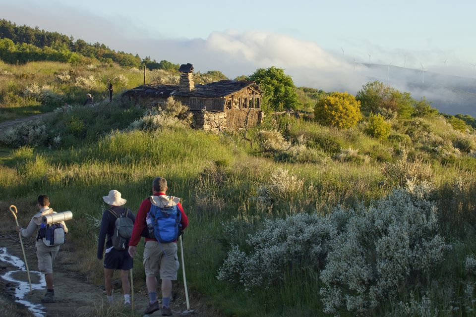 Three pilgrims near old hut, Castile and Leon, Spain