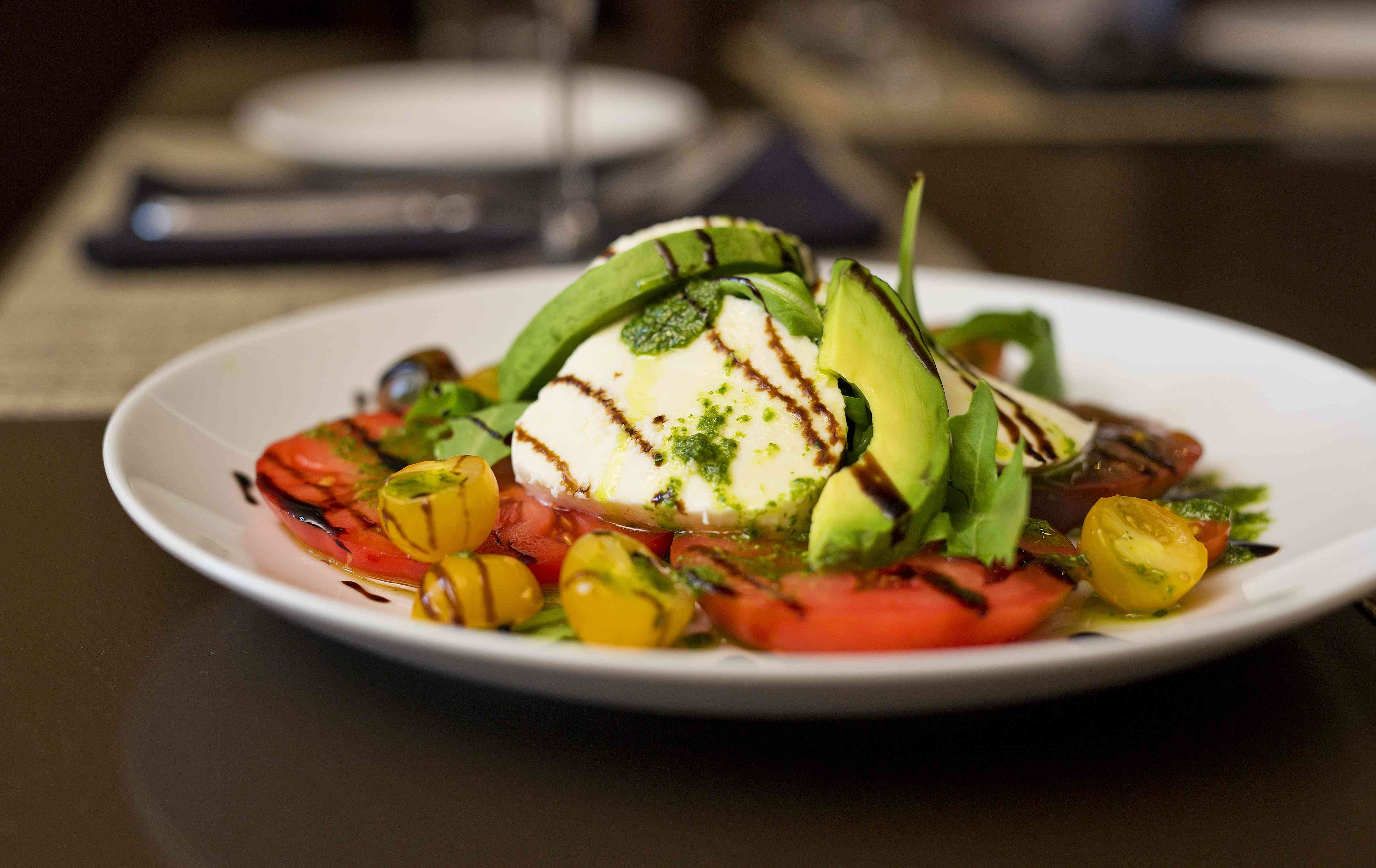 soft white cheese on a plate with sliced of avocado, tomatoes and halved cherry tomatoes drizzled with balsamic