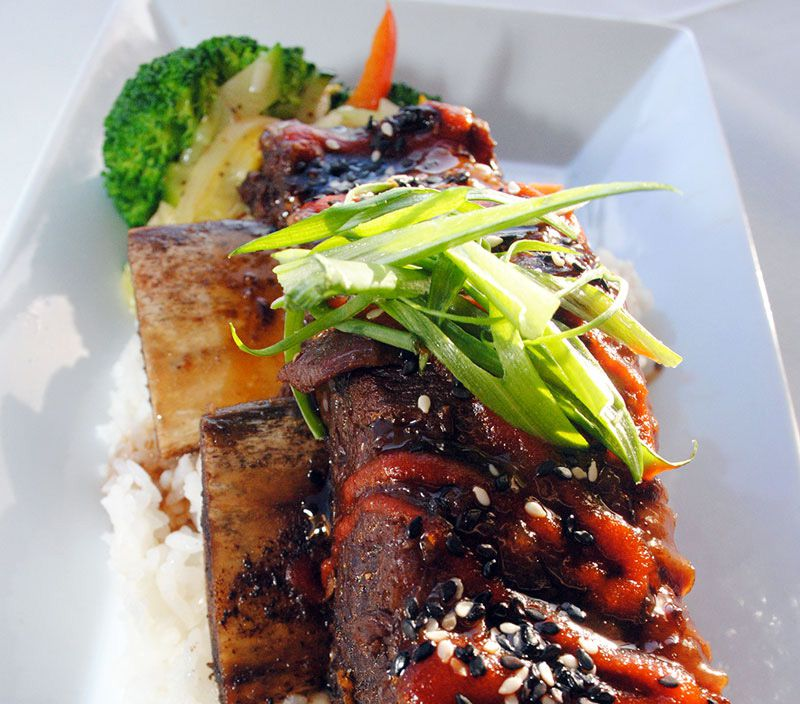 Short rib topped with black and white sesame seeds and sliced scallions