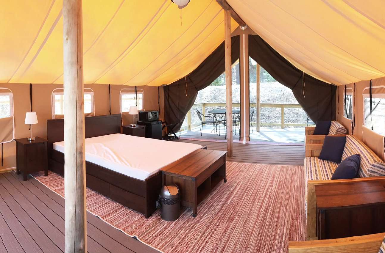 Luxury tent with a full-size bed, two night stands with lamps, a couch, two chairs and a deck outside the open tent entryway