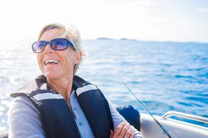blonde woman in sunglasses smiling in a boat