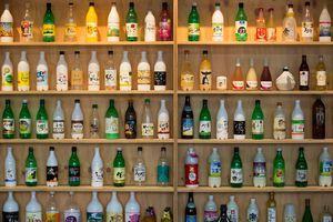 Bottles of makgeolli, Korean rice wine, on a wooden shelf