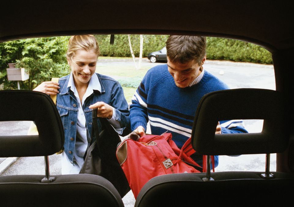 Man and woman putting bags in trunk of car