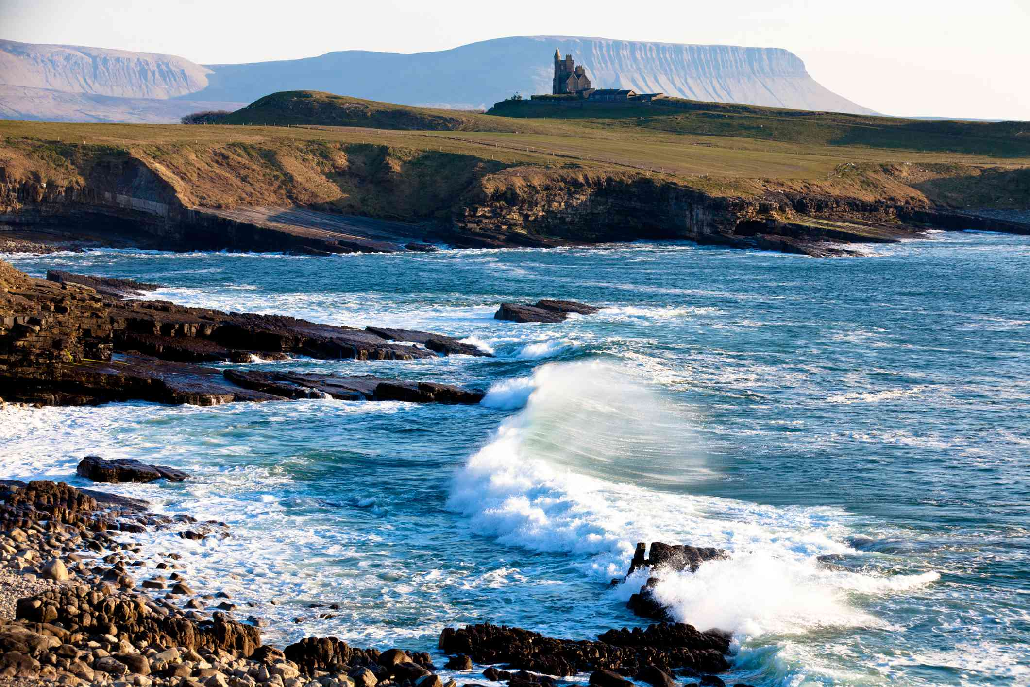 castle on a hill with waves crashing in foreground