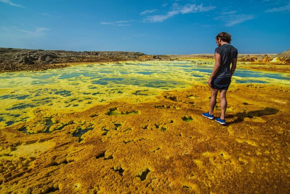 A man walks on mineral deposits at Dallol, Ethiopia