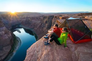 A man and a woman sit outside a tent on the edge of the Grand Canyon