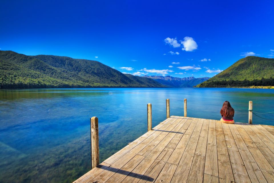 blue lake and sky with forested hills and woman sitting on a wooden jetty