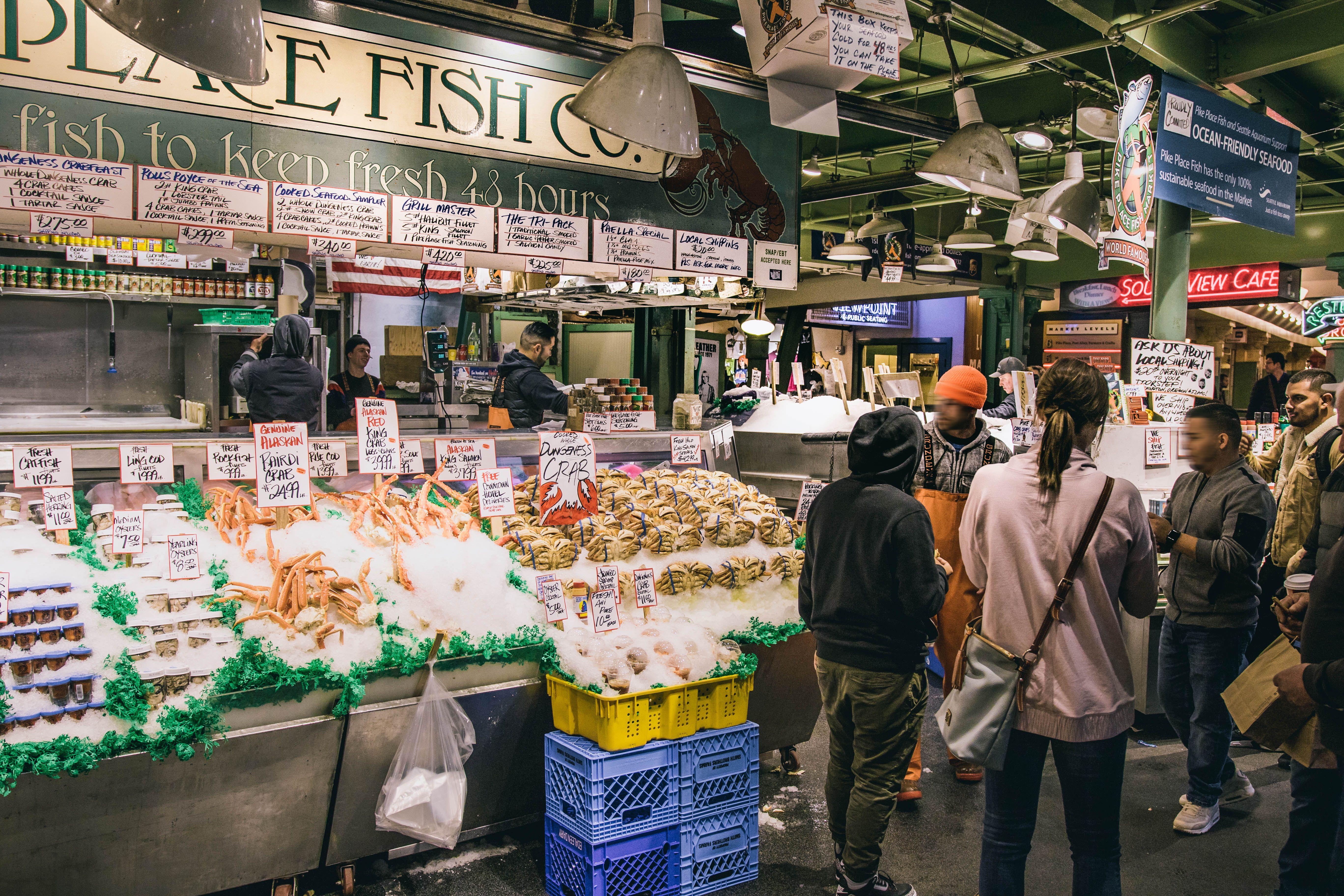 Gente comprando en un puesto de pescado en el mercado de Pike Place