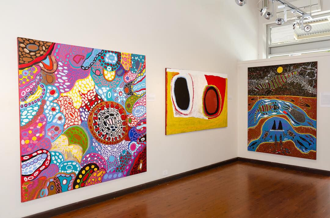Three large, colorful paintings on white walls