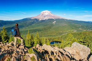 A hiker looks across an expansive forest at Mt. Hood in the distance.