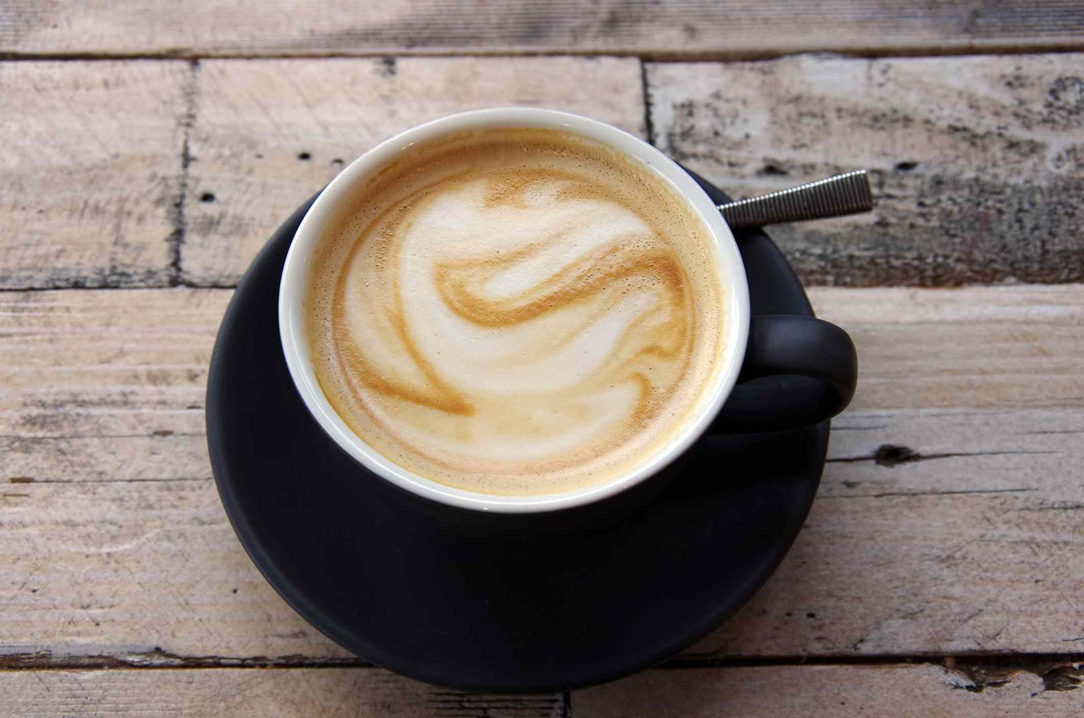 Café blanco plano en una taza negra y platillo en una mesa de café de madera