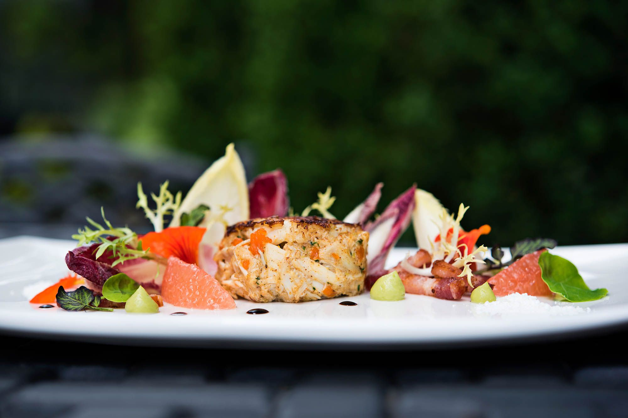 one lump crab cake on a plate with greens