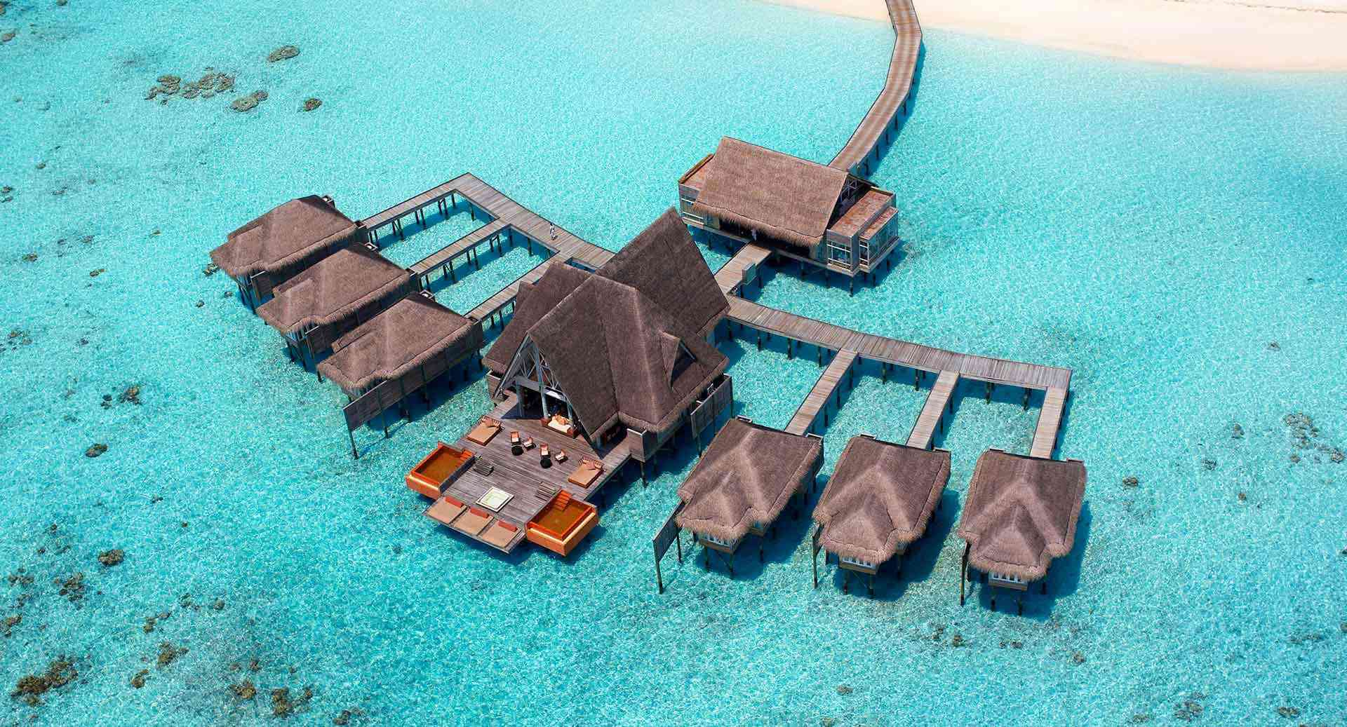 Aerial view of Overwater treatment rooms and wooden pathways at Anantara Kihavah spa