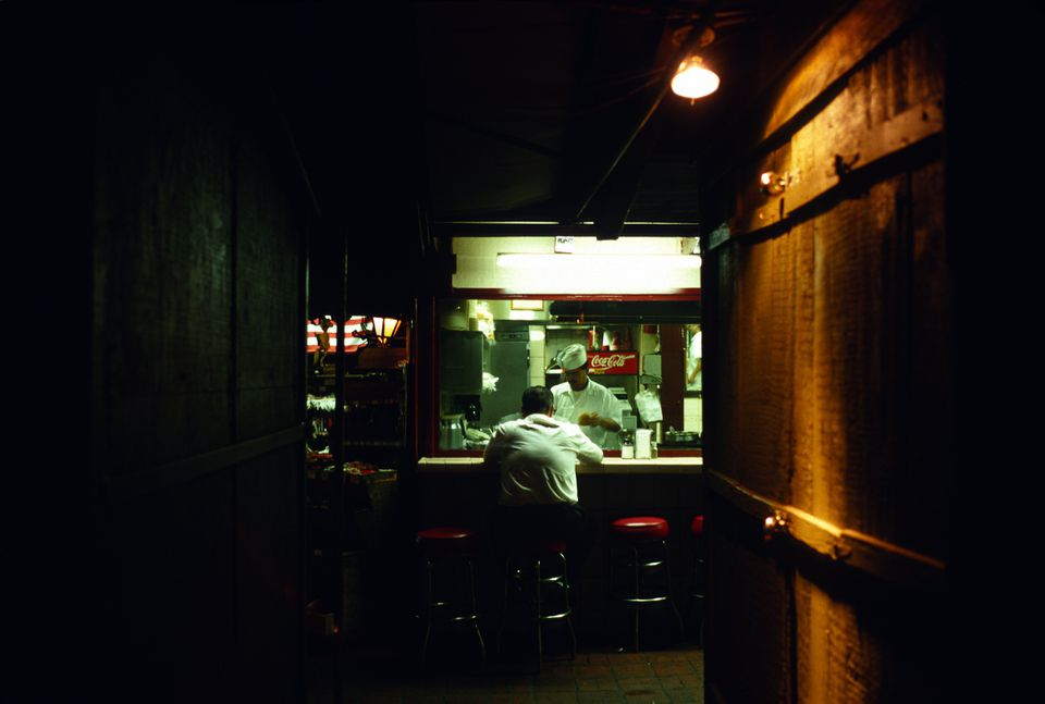 A patron sits at the bar of a taco stand late at night in central LA