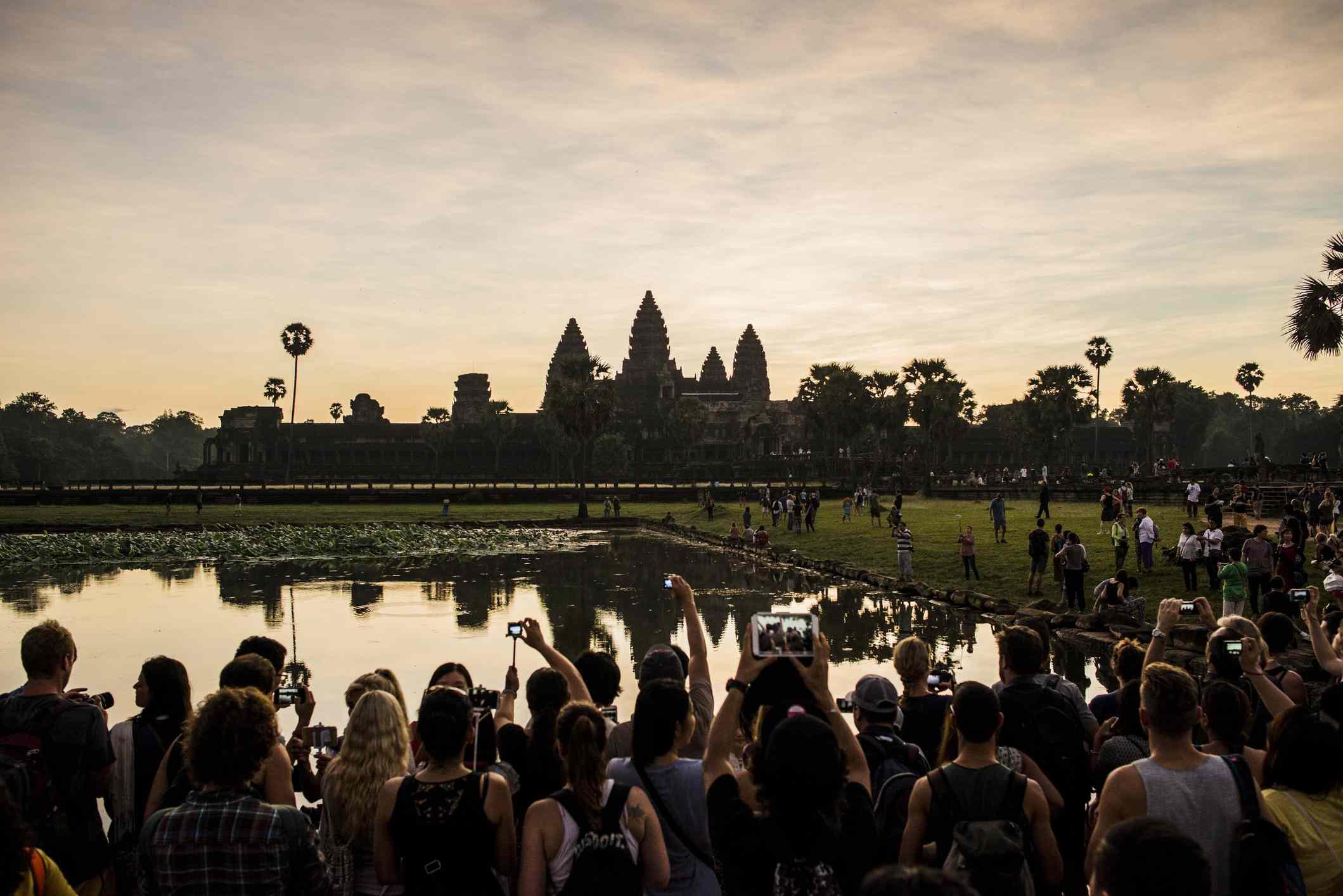 Tourists taking photos of sunrise, Angkor Wat, Siem Reap, Cambodia