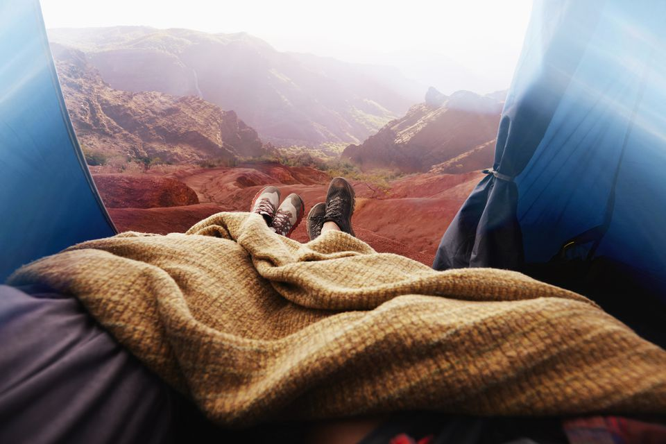 Legs of couple in camping tent in rocky landscape