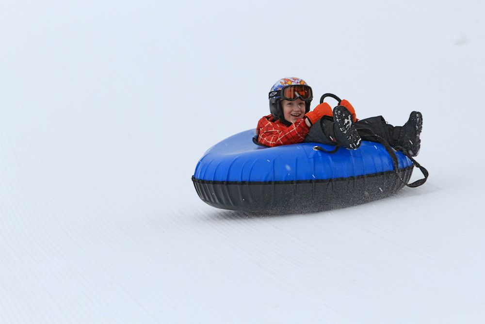 A child slides down a snowy hill in an inner tube.
